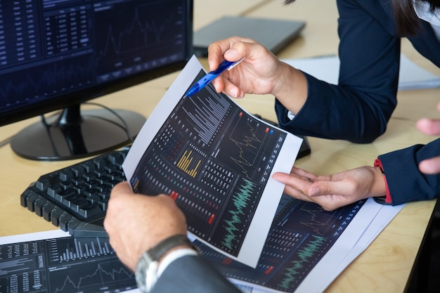 Brokers discussing trading strategy, holding papers with financial data, pointing pen at charts. cropped shot. broker job or stock market exchange concept