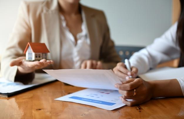 ブローカー住宅販売はテーブルに取り組んでいます。彼は手にペンと家のモデルを保持しています。