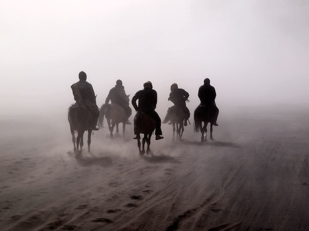 Bromo desert and horse riders during sand storm in bromo