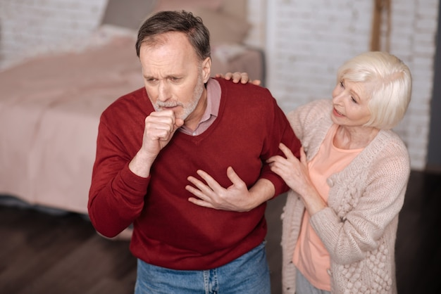 다시 기관지염. 그의 아내가 그를 지원하는 동안 서서 강하게 기침하는 수석 남자.