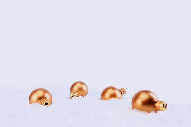 Бронзовые елочные шары в снегу, изолированные на белом фоне Premium Фотографии