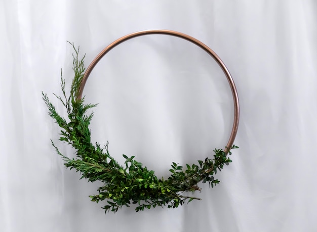 Bronze circle with boxwood greens and christmas tree on white