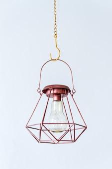 Промышленная геометрическая лампа бронзового цвета на белом фоне