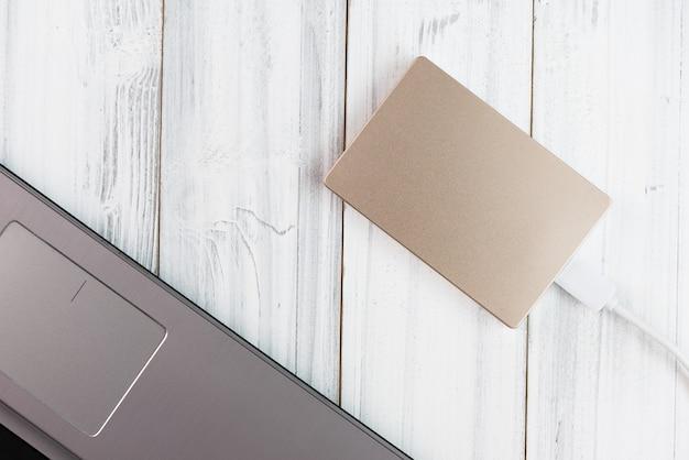 Бронзовый внешний жесткий диск на белом деревянном столе, вид сверху