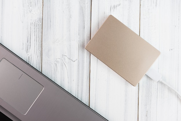 Bronze external hard drive on white wooden table, top view
