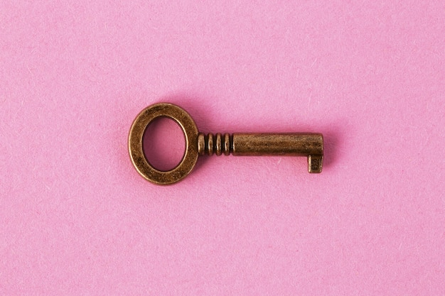 Bronze key on gently pink paper, background image