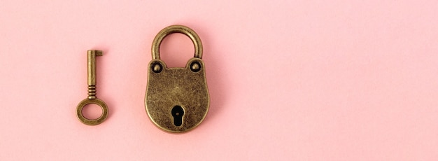 Bronze key and padlock on gently pink paper,