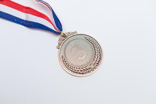 Бронзовая медаль спортивных достижений, занявшая третье место, на белом фоне. олимпийские игры и спортивная концепция
