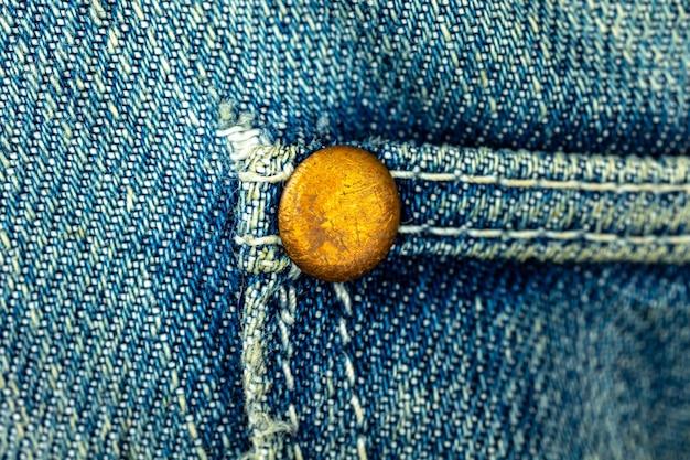 파란색 데님 청바지에 청동 금속 리벳, 주머니 솔기가 박힌, 클로즈업 배경