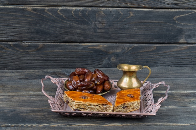 In a bronze plate dates, a jug and baklava with walnuts