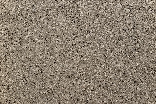 小さなスパンコール、クローズアップからブロンズの輝く背景。ホイルから茶色の金属紙の背景。