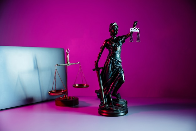 Bronze statue lady justice holding scales and sword in notary office.