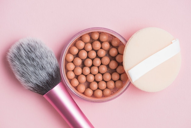 Bronzing pearls; sponge and makeup brush on pink backdrop