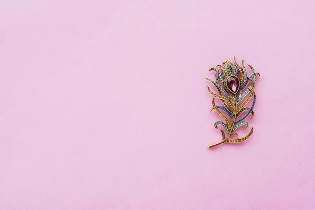 紫色の背景に孔雀の羽の形をしたブローチ