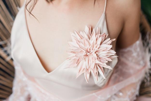 Брошь на платье. брошь из цветка. молодая девушка в легком платье. платье в стиле нижнего белья. выборочный фокус.