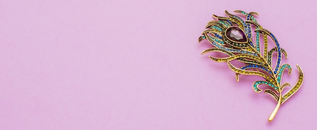 Brooch in the shape of peacock feather on purple background