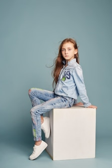 Brooding beautiful girl sitting on a white cube and posing, school models