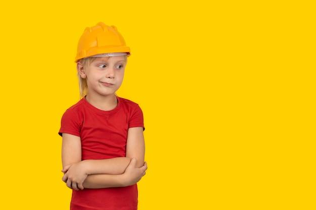 Задумчивый маленький мальчик в оранжевом шлеме на желтой стене