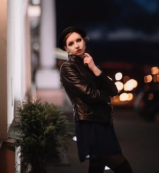 밤 도시의 불빛을 바라보는 우울한 젊은 여성.
