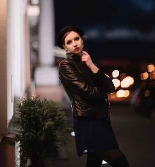 Brooding young woman looking at the lights in the night city.