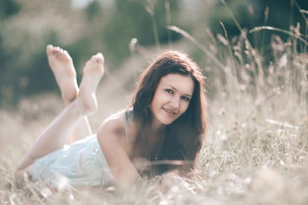 夏の日に草の上に横たわっている陰気な若い女性。