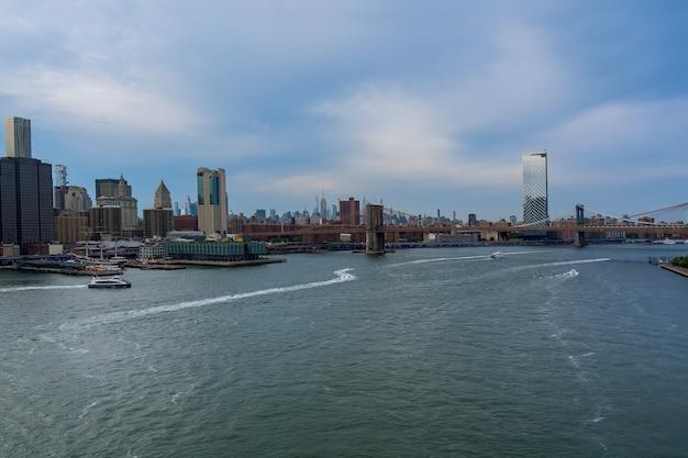 Бруклинский мост и манхэттенский мост с небоскребами манхэттена нью-йорка горизонты города над рекой гудзон сша