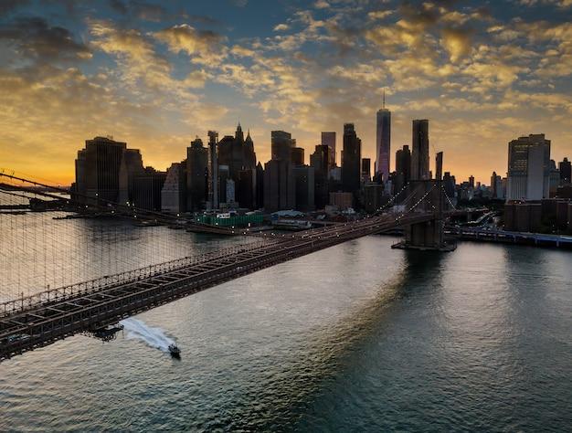 Бруклинский мост и манхэттен через ист-ривер на закате, нью-йорк, сша