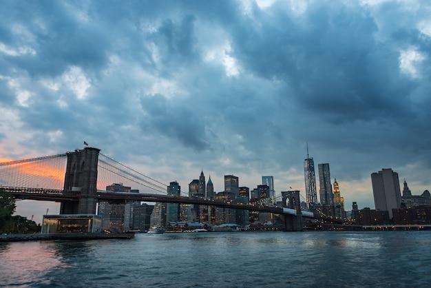 Бруклинский мост и горизонт нью-йорка через ист-ривер в сумерках дождливым летним днем