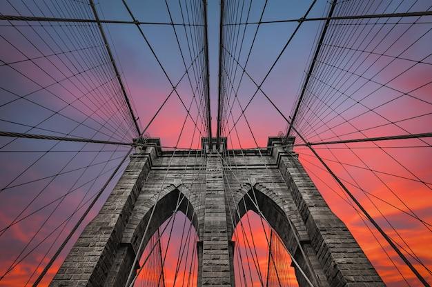 Бруклинский мост в нью-йорке против драматического закатного неба с облаками