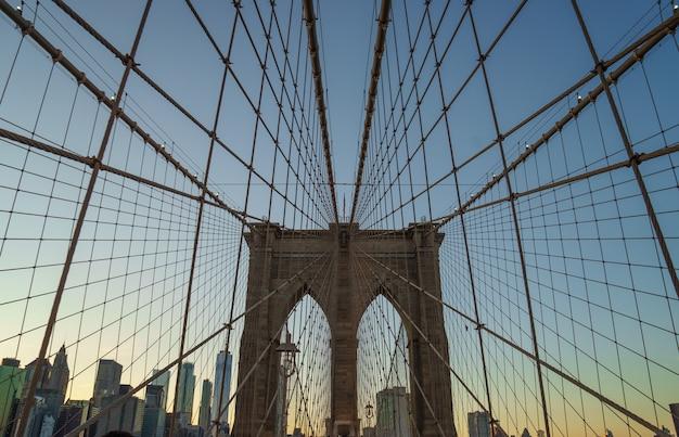 Бруклинский мост в нью-йорке с геометрической перспективой на закате.