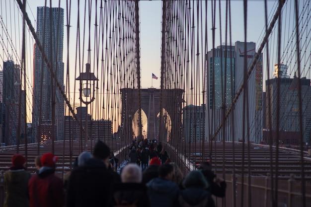 Бруклинский мост в нью-йорке с размытыми людьми на закате.
