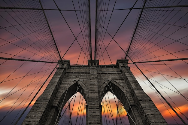 Brooklyn bridge in new york city against dramatic sunset sky with clouds