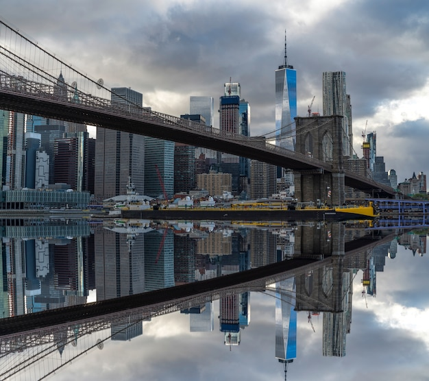 Brooklyn bridge on new york with reflection of skycrapers on the thames