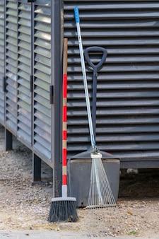 Метла и лопата - инструменты дворника. дворники на рабочем месте.