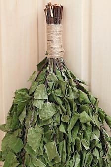 Веник из березовых веников для русской бани. на деревянной поверхности.