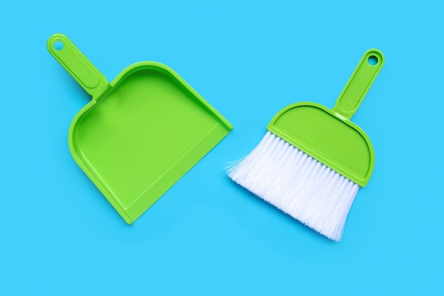 A broom and dustpan on blue background. top view
