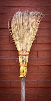 Broom on wooden handle stands near a brick wall