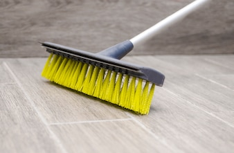 Broomstick yellow plastic fibers cleaning the floor.Housekeeping and sweeping with broom
