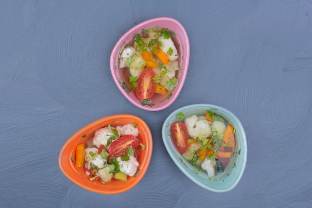 Broth soup in multicolor cups with chopped vegetables