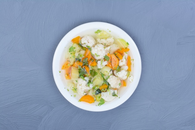 Broth soup with chopped and minced vegetables in a white plate.
