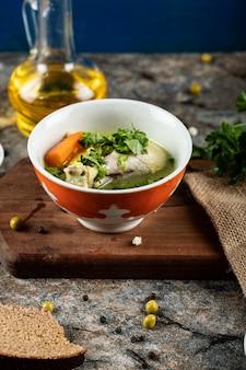 赤いボウルにハーブ、ポテト、ニンジンのスープ