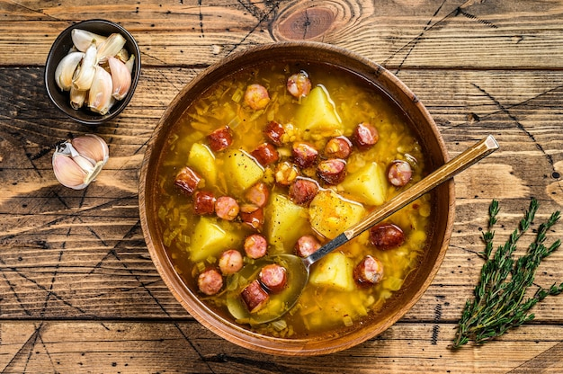 Broth split pea soup with smoked sausages in a wooden plate