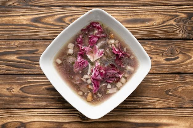 Бульон с салатом из бекона и радиккио в белой керамической тарелке