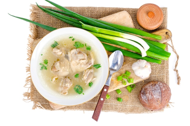 Broth with chicken meat isolated on white