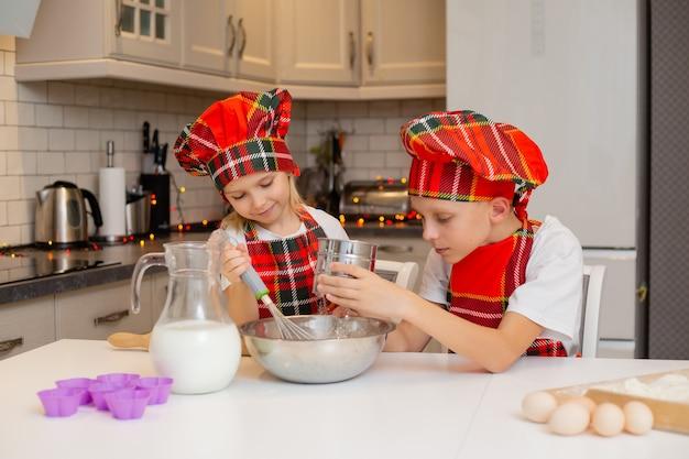 兄と妹はキッチンでお祝いディナークッキーを調理しています新年冬のコンセプト