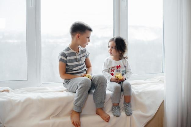 Брат и сестра сидят на подоконнике, играют и едят яблоки. счастье.