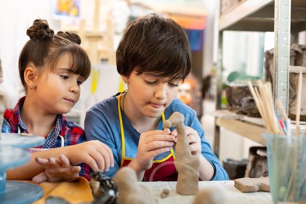 粘土の動物をモデリングするアートレッスンの兄と妹