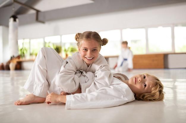 Брат и сестра. веселые позитивные брат и сестра чувствуют себя счастливыми, занимаясь айкидо вместе