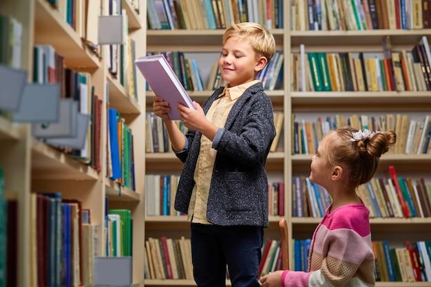 형제 자매는 도서관에서 책을 선택하고 대화를 나누며 학교 도서관에서