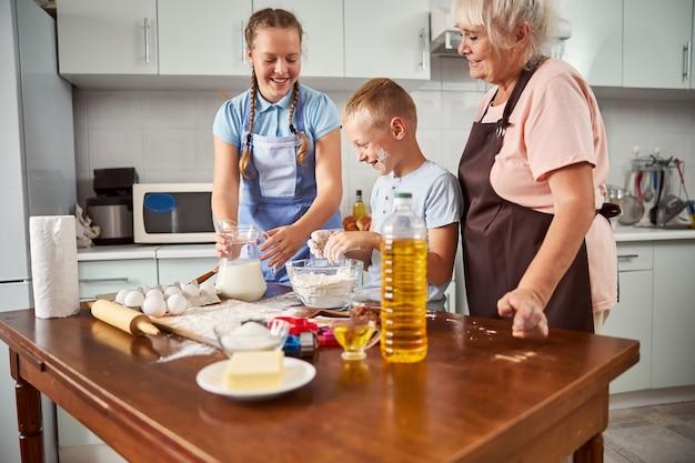부엌에서 할머니와 함께 요리하는 형제와 자매